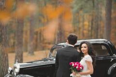 Как раз пожененные пары в роскошном ретро автомобиле на их день свадьбы Стоковые Фото