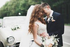 Как раз пожененные пары в роскошном ретро автомобиле на их день свадьбы Стоковые Изображения RF