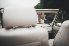 Как раз пожененные пары в роскошном ретро автомобиле на их день свадьбы Стоковое Изображение RF