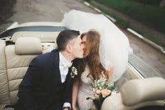 Как раз пожененные пары в роскошном ретро автомобиле на их день свадьбы Стоковая Фотография