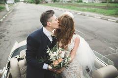 Как раз пожененные пары в роскошном ретро автомобиле на их день свадьбы Стоковое фото RF
