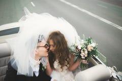 Как раз пожененные пары в роскошном ретро автомобиле на их день свадьбы Стоковое Фото