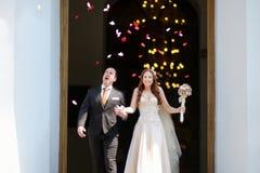 Как раз пожененные пары под дождем лепестков цветка Стоковое фото RF