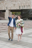 Как раз пожененные любящие пары в платье и костюме свадьбы Бежать счастливого жениха и невеста идя в городе лета Стоковая Фотография