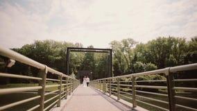 как раз поженено Backview невесты и groom в свадьбе оборудует идти на мост держа руки в летнем времени видеоматериал