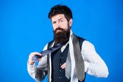 Как соответствовать галстуку рубашке и костюму Владение хипстера человека бородатое немногие галстуки на голубой предпосылке Гай  стоковые изображения