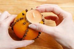 Как сделать оранжевый шарик pomander с свечой - консультацией Стоковые Изображения RF