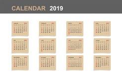 Календарь 2019 - комплект ежемесячного календаря на коричневой бумаге и белой деревянной предпосылке иллюстрация штока