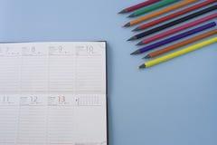 Календарь с организованными crayons в угле на пастельной сини стоковые изображения rf