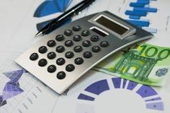 Калькулятор, 100 евро и ручка лежа на диаграммах Стоковое Изображение RF