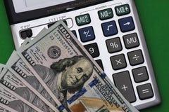 Калькулятор и валюта на зеленой предпосылке Стоковая Фотография RF