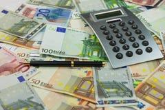 Калькулятор и деньги лежат на предпосылке евро Идеи и концепции дела Стоковые Изображения