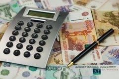 Калькулятор и деньги лежат на предпосылке рублей Идеи и концепции дела Стоковое фото RF