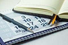 Калькулятор и тетрадь дела на предпосылке календаря стоковая фотография