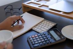 калькулятор пользы человека делает примечание с высчитывает о цене в offi стоковые изображения