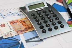 Калькулятор, пять тысяч рублей и ручка лежа на диаграммах Стоковые Изображения