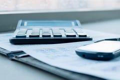 Калькулятор, смартфон и финансовые документы на деле стоковые фотографии rf