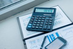 Калькулятор, смартфон и финансовые документы на деле стоковое фото