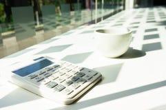 Калькулятор с кофе в офисе Стоковое Фото