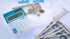Калькулятор с японскими бумажными деньгами иен валюты и монетка на ребре Стоковые Изображения