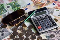 Калькулятор, ballpen, бумажник и немногие монетки на серии денег бумаги стоковая фотография rf