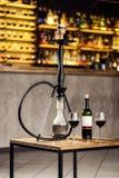 Кальян на воде стоит на деревянном столе с бутылкой красного цвета стоковое изображение rf