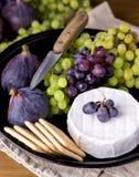 Камамбер бри сыра с смоквами и виноградинами на еде деревянного стола для смокв вина зеленых и закусок Ver плиты ножа шутих красн стоковые изображения