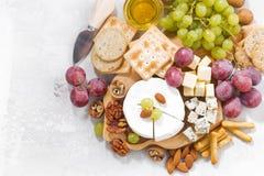 Камамбер, виноградины и закуски на белой таблице, взгляд сверху Стоковая Фотография
