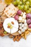 Камамбер, виноградины и закуски на белой предпосылке, взгляд сверху Стоковое фото RF