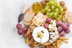 Камамбер, виноградины и закуски на белой предпосылке, взгляд сверху Стоковые Изображения