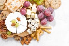 камамбер, виноградины и закуски на белой таблице, взгляд сверху, крупном плане Стоковое фото RF