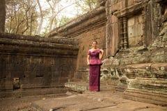 Камбоджийская девушка в платье кхмера готовит каменную стену в Angkor Thom стоковые изображения rf