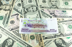Камбоджийский Riel (KHR) на предпосылке много долларов Стоковые Изображения