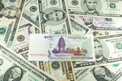 100 камбоджийских Riel (KHR) на предпосылке много долларов Стоковые Фото