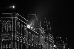КАМЕДЬ магазина на предпосылке деревьев украшенных с шариками рождества красный квадрат ноча moscow Россия Стоковое Фото