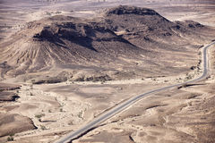 Каменистая пустыня landscapes с вымощенной дорогой, Сахарой. Стоковое Изображение