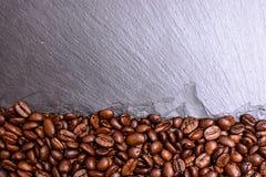 Каменистая черная доска взбрызнутая с близрасположенным зерном зажарила в духовке кофе, место для tex, предпосылку и текстуру Стоковое Изображение