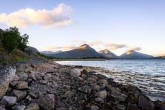 Каменистый берег с горами Стоковая Фотография RF
