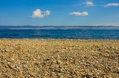 Каменистый пляж и голубое море Стоковая Фотография RF
