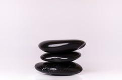 Каменная обработка Черные массажируя камни на белой предпосылке горячие камни Баланс Дзэн любит концепции Камни базальта Стоковые Изображения