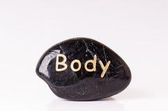 Каменная обработка Черные массажируя камни на белой предпосылке горячие камни Баланс Дзэн любит концепции Камни базальта Стоковые Изображения RF