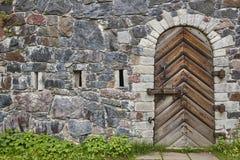 Каменная стена с дверью античного замка запертой деревянной Винтаж стоковые фото