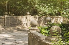 Каменное приложение вдоль дороги в старом парке, украшенном с шариками штукатурки и камня стоковое фото