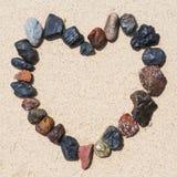 Каменное расположение как рамка сердца на пляже Стоковое Изображение RF