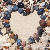 Каменное расположение как рамка сердца на пляже Стоковые Изображения RF