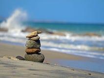 Каменные башенки на пляже с волнами на заднем плане, концепция баланса и сработанность стоковое изображение rf