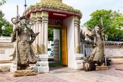 Каменные высекая гиганты перед стробом Wat Pho в Бангкоке стоковые изображения