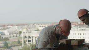 Каменные каменщики в кирпичах положения шлемов на стене против города сток-видео