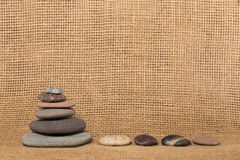 Каменные пирамида из камней и камни на предпосылке мешковины Стоковая Фотография RF