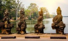 Каменные статуи богов и демонов на мосте к южному стробу в комплексе Angkor Thom, Siem Reap, Камбоджи стоковые фотографии rf